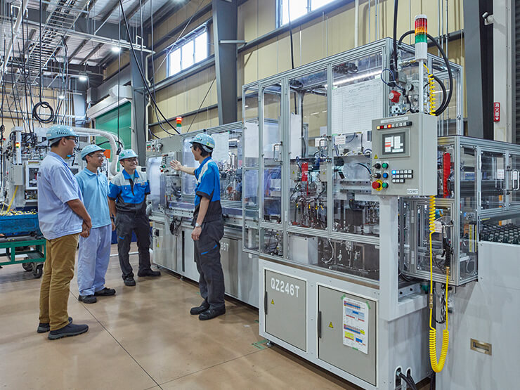 Overseas employees receiving technical guidance at a new production facility